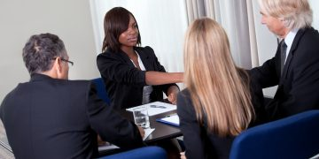 Mature group of business managers conducting job interview shaking hands with applicant at a table in meeting room